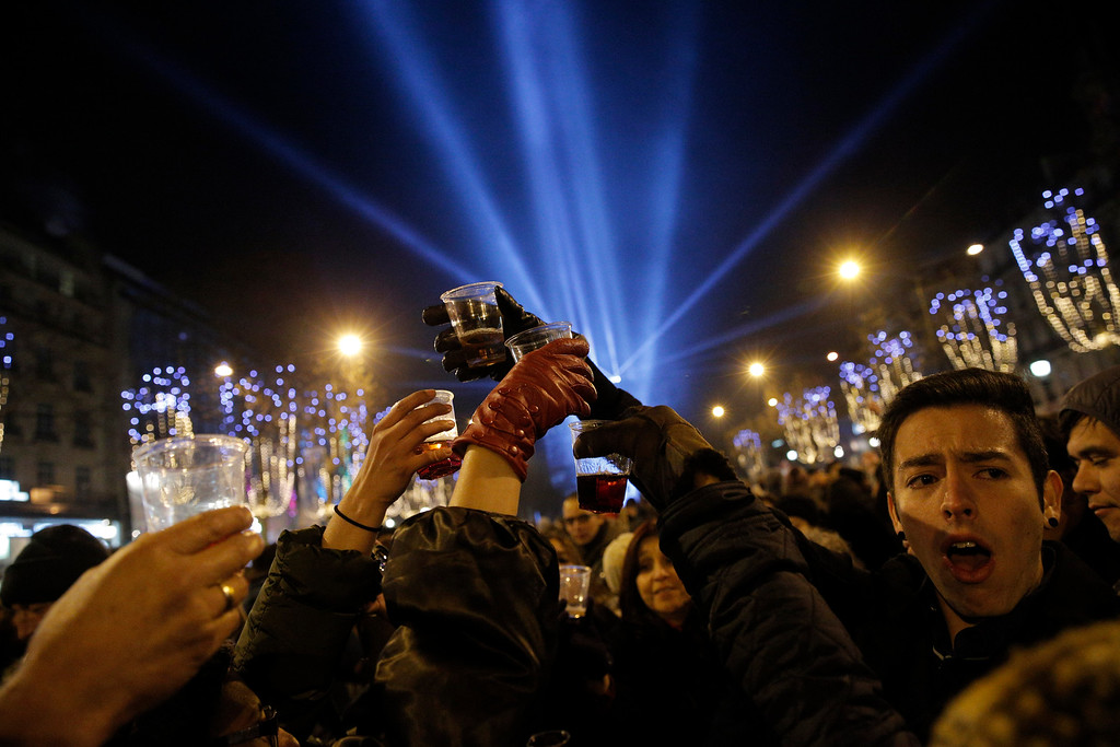 . Revellers celebrate the New Year\'s Eve on the Champs Elysees avenue in Paris, France, Thursday, Jan. 1, 2015. The Arc de Triomphe is illuminated in the background. (AP Photo/Christophe Ena)