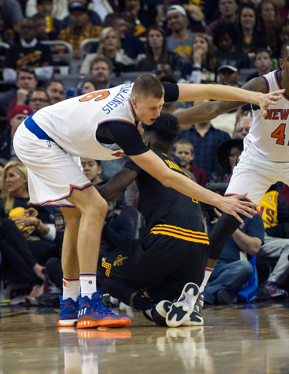 . Cleveland Cavaliers\' Iman Shumpert runs in to New York Knicks\' Kristaps Porzingis (6) during the second half of a n NBA basketball game in Cleveland, Tuesday, Oct. 25, 2016. Shumpert was injured on the play and left the game. The Cavaliers won 117-88. (AP Photo/Phil Long)