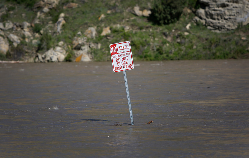 A 'No Parking' sign stands surrounded by water as the Yellowstone River swells beyond the banks at Coulson Park in Billings, Mont. on May 24, 2018.