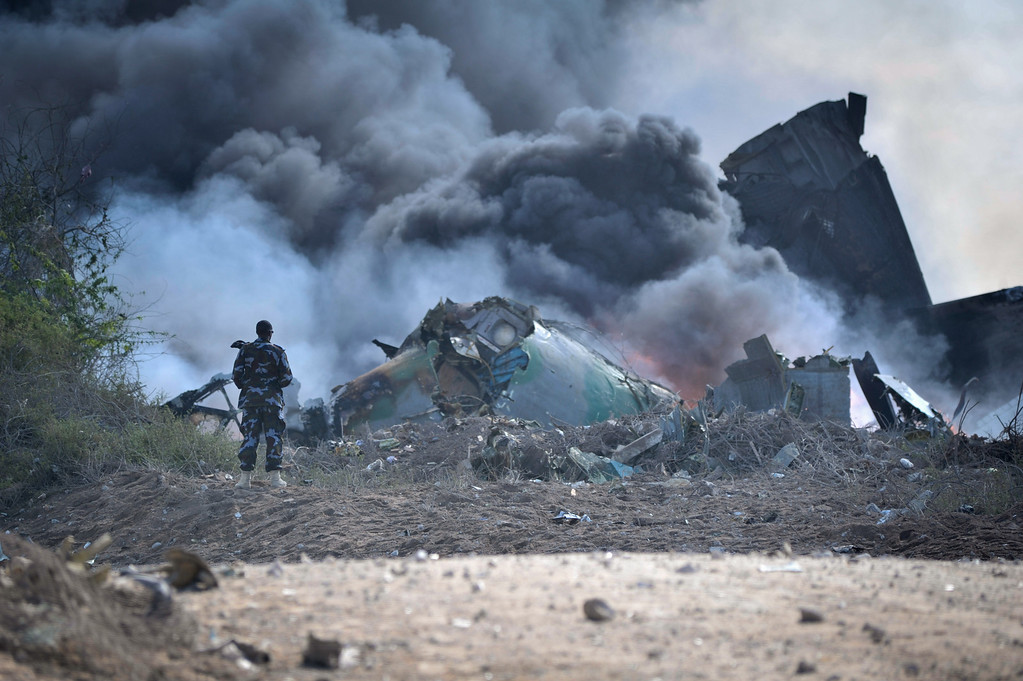 . In this handout photo released by African Union Mission in Somalia (AMISOM), AMISOM firefighters attempt to extinguish the fire at the site of an airplane crash in Mogadishu, Somalia, Friday, Aug. 9. 2013.  (AP Photo/Tobin Jones, AU/UN IST, AMISOM)