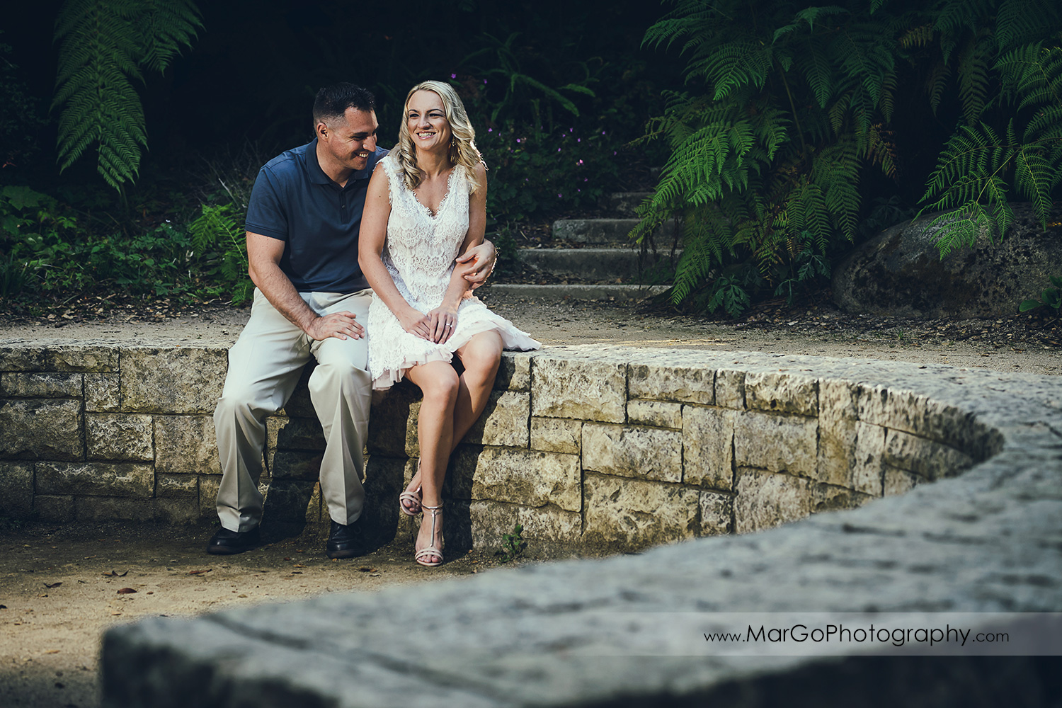 portrait of man in navy blue shirt and woman in white dress sitting on stone wall during engagement session at San Francisco Golden Gate Park