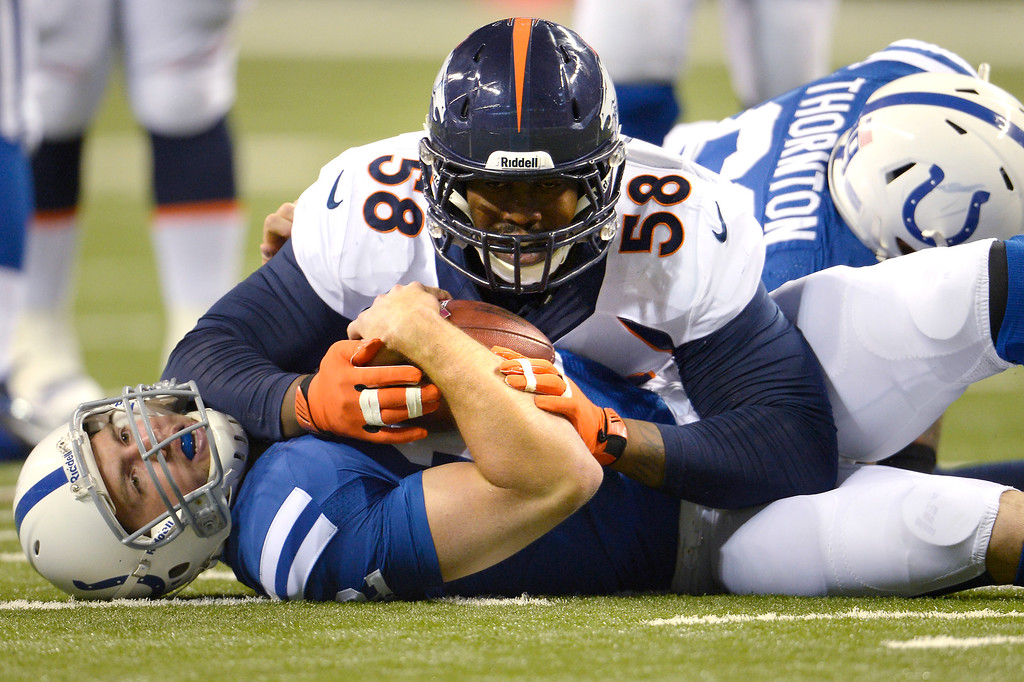 . Outside linebacker Von Miller (58) of the Denver Broncos covers quarterback Andrew Luck (12) of the Indianapolis Colts and the ball after a sack in the first half at Lucas Oil Stadium. October 20, 2013 Indianapolis, Indiana. (Photo By Joe Amon/The Denver Post)