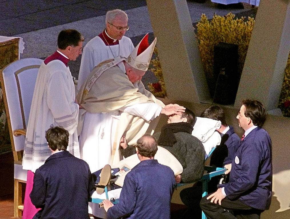 ". Pope John Paul II gives a special blessing by placing his two hands on the head of a man who was carried  on a stretcher up the steps of St. Peter\'s Basilica during an open-air special Jubilee Celebration for the Sick and for Health Care Workers in St. Peter\'s square at the Vatican in this Feb. 11 2000 file photo.  Bit by bit over his 26-year papacy, John Paul has built a rich body of reference about the final stages of life. Its pillars include categorical rejection of euthanasia, insistence on treatments that help people bear ailments with dignity and encouragement of research to ""enhance and prolong human life.\"" But some gray areas remain. There\'s room in the pope\'s view to refuse some forms of aggressive medical intervention for terminally ill patients and avoid painkillers that induce unconsciousness. (AP Photo/Pier Paolo Cito/File)"