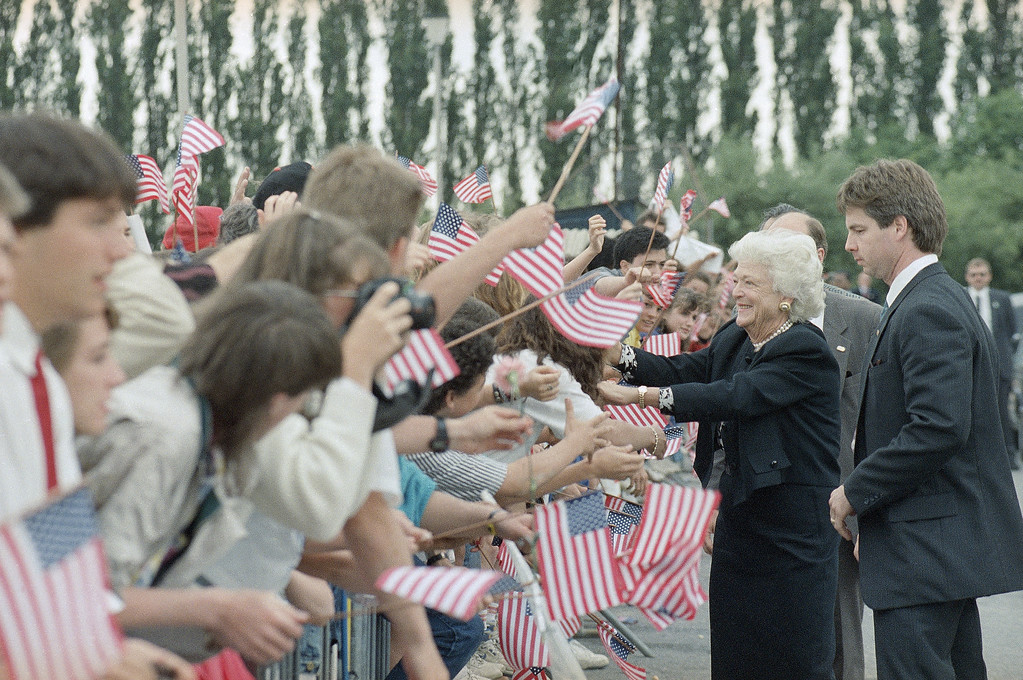 . U.S. first lady Barbara Bush makes her way through a crowd of flag-waving members of the American Community of Brussels after paying a visit to the Brussels American School, Tuesday, May 30, 1989 in Brussels, Belgium, before accompanying President Bush to West Germany. (AP Photo/Ron Edmonds)