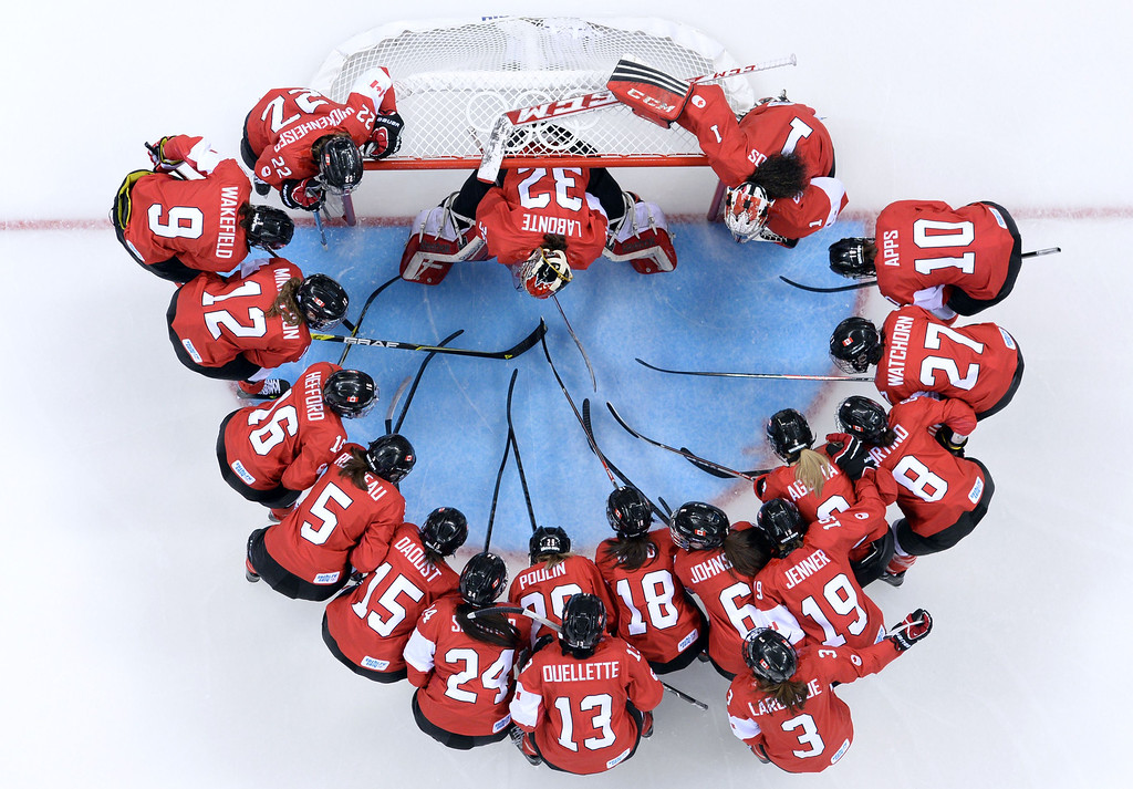 . Canada\'s player gather before the start of the Women\'s Ice Hockey Group A match between Canada and USA at the Sochi Winter Olympics on February 12, 2014 at the Shayba Arena. AFP PHOTO / JONATHAN  NACKSTRAND/AFP/Getty Images