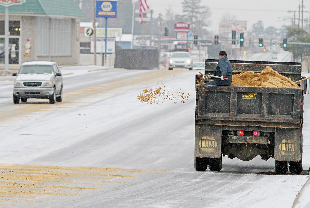 . A worker with the El Dorado Street Department tosses sand out of a dump truck on Wednesday, Feb. 12, 2014, in El Dorado, Ark. Most businesses around El Dorado opted to open later in the day after a winter storm dumped a wintery mix on the area. (AP Photo/The El Dorado News-Times, Michael Orrell)