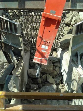 NPK PH4 hydraulic hammer on a pedestal boom with enviro bracket breaking oversized rock at the crusher.jpg