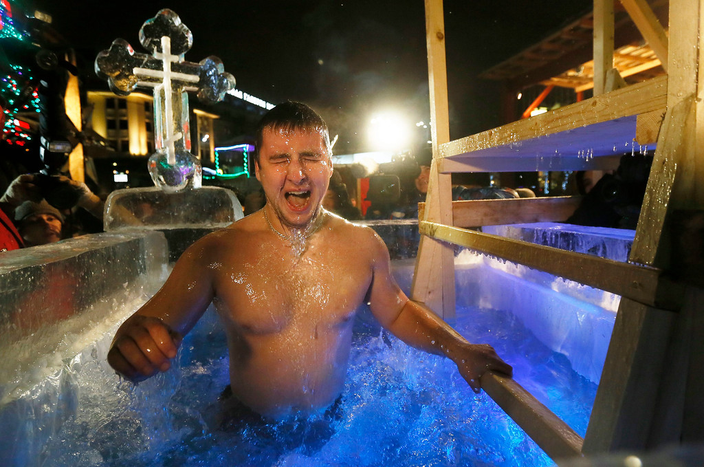 . A Russian man reacts as he dips into a bassin with ice water during the celebrations of the Orthodox Epiphany holiday in the center of Moscow, Russia, 18 January 2014. Orthodox believers traditionally jump into cold water to purify their souls. Temperatures in Moscow dropped to below minus 15 degrees Celsius on 18 January 2014.  EPA/YURI KOCHETKOV