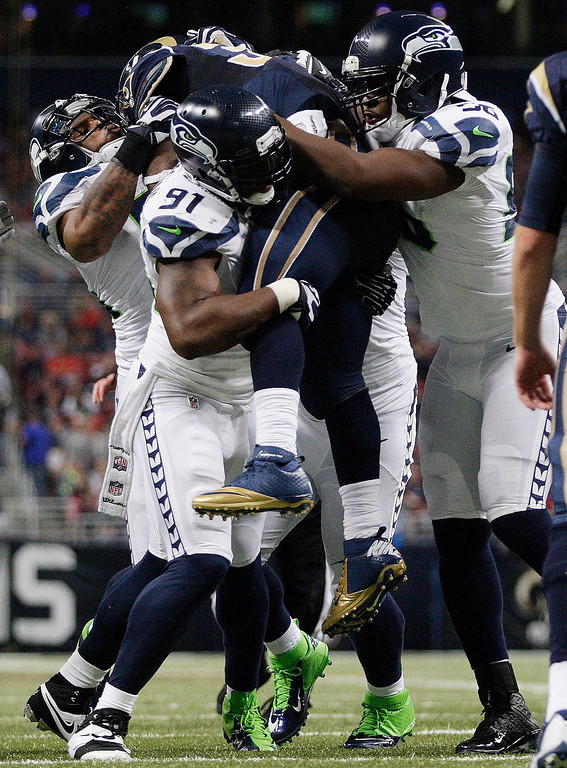 . Seattle Seahawks\' Chris Clemons (91) picks up St. Louis Rams running back Zac Stacy (30) as Bobby Wagner, left, and Cliff Avril team up during the first half of an NFL football game, Monday, Oct. 28, 2013, in St. Louis. (AP Photo/Tom Gannam)
