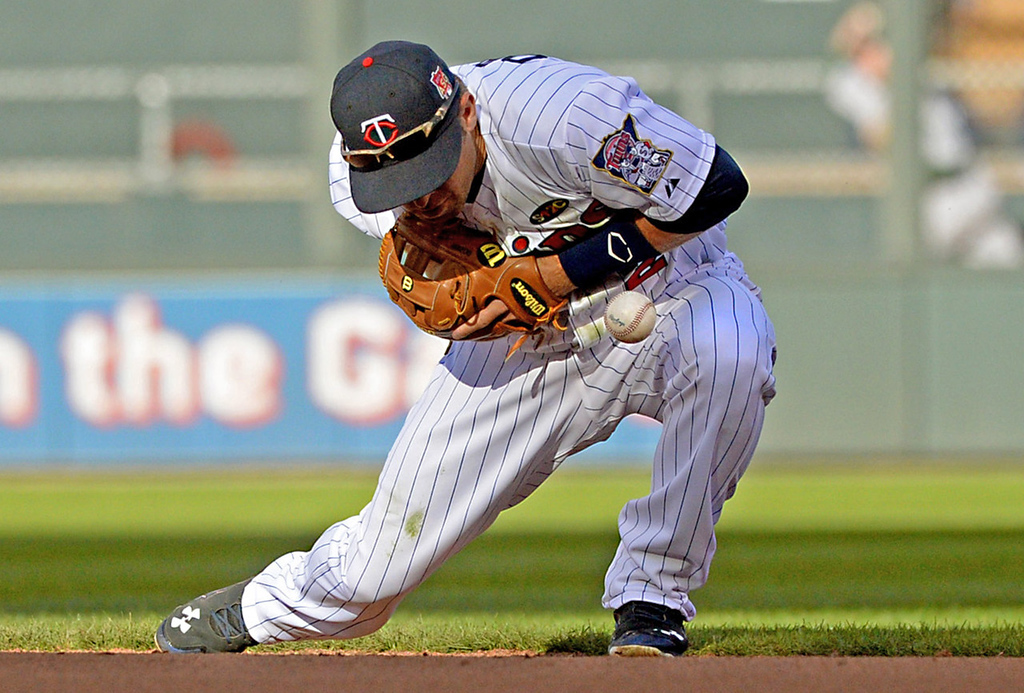 . Minnesota second baseman Brian Dozier uses his body to stop a sharp Oakland grounder by Oakland\'s Eric Sogard for the putout in the eighth inning. (Pioneer Press: John Autey)