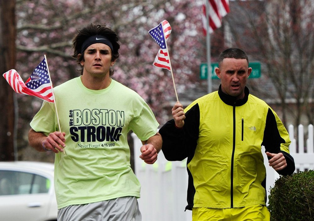 Description of . Mike Coppola (L) and Eric Wayne run by Franklin Street with American flags and a 'Boston Strong' t-shirt on April 20, 2013 in Watertown, Massachusetts. A manhunt for Dzhokhar A. Tsarnaev, 19, a suspect in the Boston Marathon bombing ended after he was apprehended on a boat parked on a residential property in Watertown, Massachusetts. His brother Tamerlan Tsarnaev, 26, the other suspect, was shot and killed after a car chase and shootout with police. The bombing, on April 15 at the finish line of the marathon, killed three people and wounded at least 170.  (Photo by Kevork Djansezian/Getty Images)