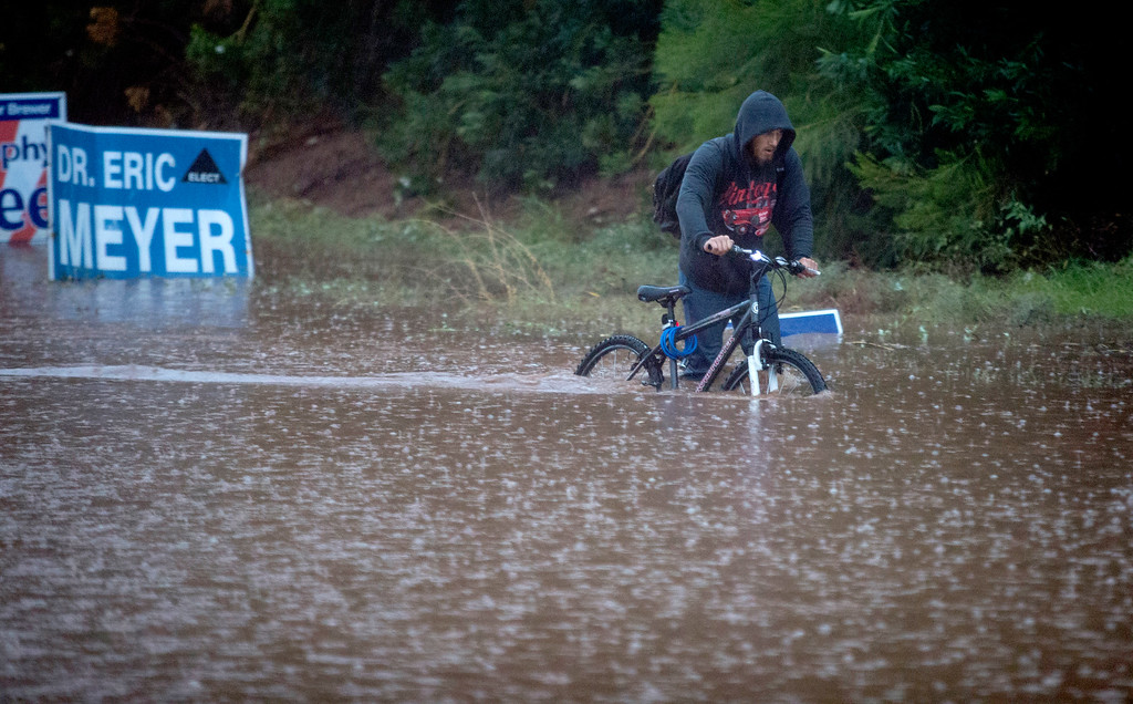 . Construction worker Jason Haight Jr. makes his way back home, through high water at 54th Street and Camelback Avenue, Monday, Sept. 8, 2014, in Phoenix. Haight and his father rode to their construction site only to find work canceled for the day. (AP Photo/The Arizona Republic, Charlie Leight)