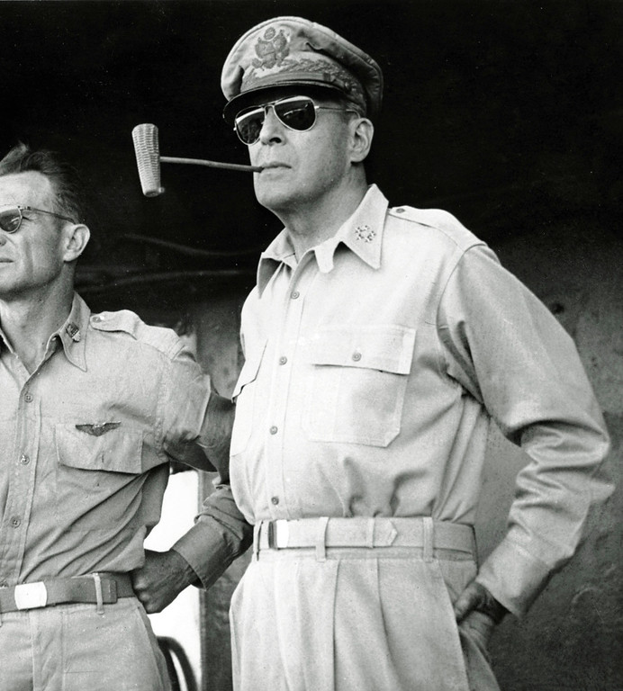 . ** FILE ** Five star Gen. Douglas MacArthur smokes one of his trademark corn cob pipes aboard a ship bound for Luzon Island in the Philippines in this Jan. 20, 1945 file photo.  A congressional committee cut Gen. MacArthur down to size in 1951, deftly exposing the flaws that had led President Harry Truman to remove him as Korean war commander. The man at left is unidentified. (AP Photo/File)