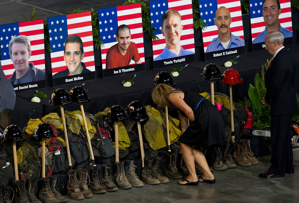 . Photos of some of the 19 fallen firefighters line the front of the stage before a memorial service at Tim\'s Toyota Center in Prescott Valley, Ariz. on Tuesday, July 9, 2013.   (AP Photo/The Arizona Republic, Michael Chow, Pool)