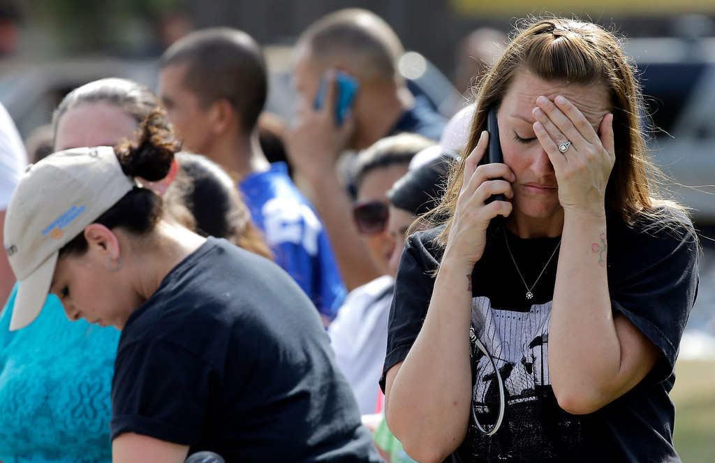 . Laurie Garza talks on the phone as she waits for her daughter outside Spring High School Wednesday, Sept. 4, 2013, in Spring, Texas. (AP Photo/David J. Phillip)