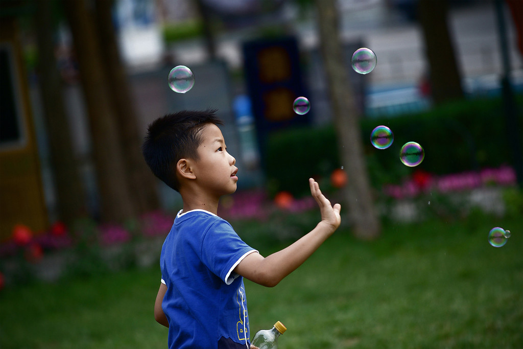 . A boy plays with bubbles at a park in Beijing on June 1, 2013 . Tens of thousands of children celebrate the International Children\'s Day in China. WANG ZHAO/AFP/Getty Images