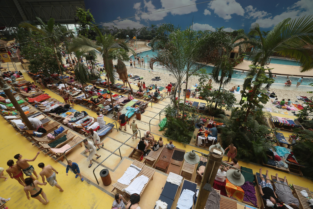 ". Visitors lounge at the ""South Sea\"" beach at the Tropical Islands indoor resort on February 15, 2013 in Krausnick, Germany. Located on the site of a former Soviet military air base, the resort occupies a hangar built originally to house airships designed to haul long-distance cargo. Tropical Islands opened to the public in 2004 and offers visitors a tropical getaway complete with exotic flora and fauna, a beach, lagoon, restaurants, water slide, evening shows, sauna, adventure park and overnights stays ranging from rudimentary to luxury. The hangar, which is 360 metres long, 210 metres wide and 107 metres high, is tall enough to enclose the Statue of Liberty.  (Photo by Sean Gallup/Getty Images)"