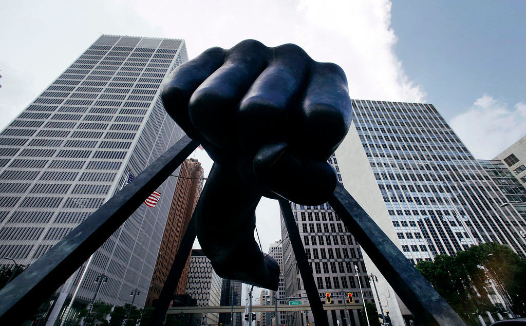 """. In this July 18, 2013 file photo, the Detroit skyline rises behind the Monument to boxer Joe Louis, also known as \""""The Fist.\"""" The sculpture is an icon in Detroit�s downtown, which is in the very early stages of recovery following finalization of the city�s bankruptcy. (AP Photo/Paul Sancya)"""