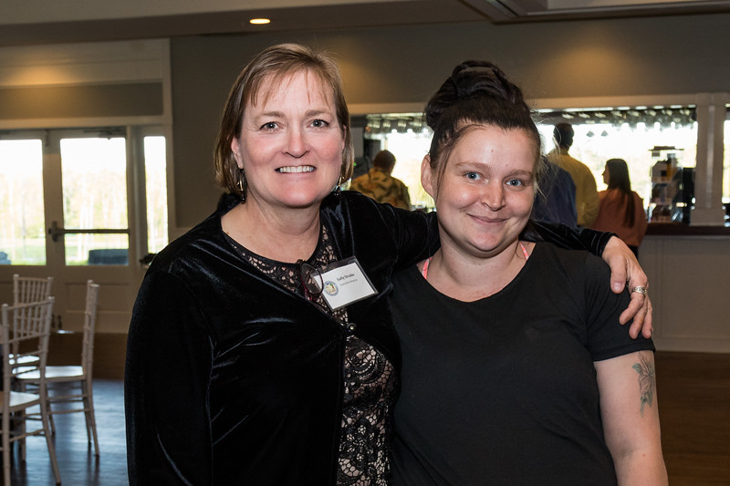 Executive Director Sally Struble, left, and former shelter resident Jessica Danforth-Babb, right, celebrate at the Homeless Center for Strafford County's Spring Fling Fund Raiser Friday night in Somersworth. [Scott Patterson/Fosters.com]