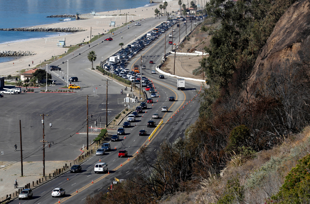 . Traffic moves slowly on Pacific Coast Highway in the Pacific Palisades area of Los Angeles Wednesday, Jan. 15, 2014, after a fire threatened bluff top homes Tuesday afternoon. As Santa Ana winds made moisture plunge, plant life wither and wildfire danger soar, Southern California firefighters pounced on several small blazes before they could surge, though another day of dryness awaited.  (AP Photo/Reed Saxon)