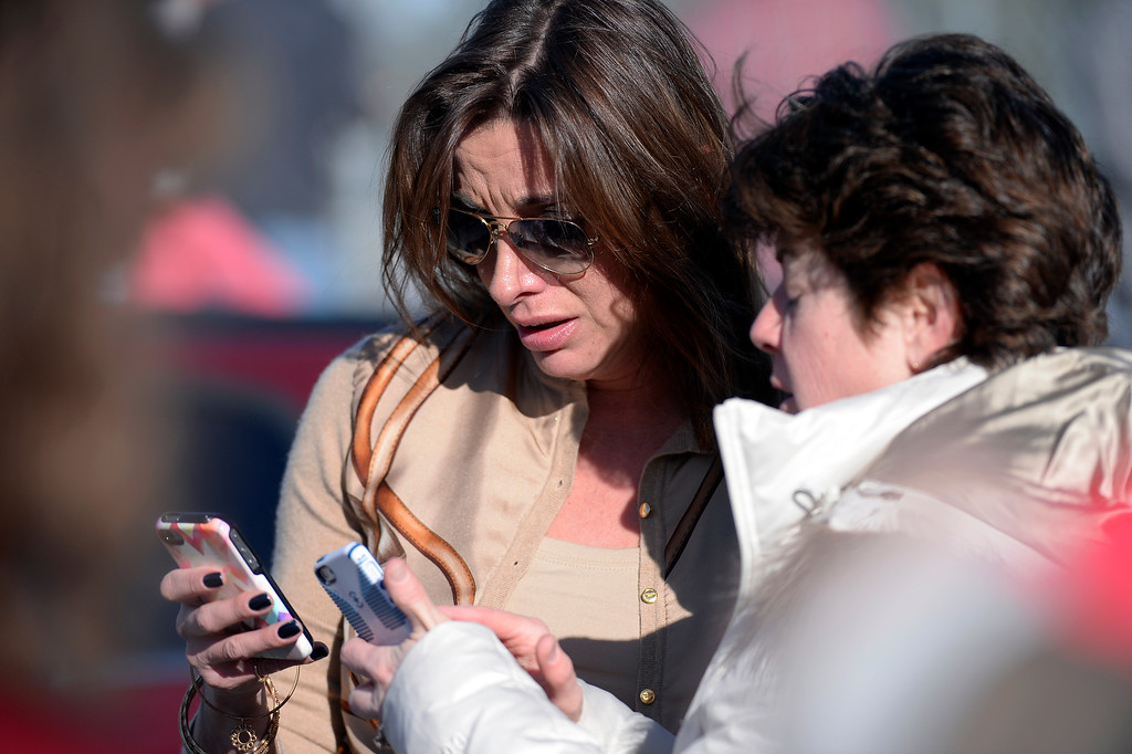 . CENTENNIAL, CO - Parents check their phone hoping to get a text from their child. Students who were able to get out were standing out side on the football field. A gunman, who was student at the school was spotted inside Arapahoe High School December 13, 2013. The gunman was targeting a teacher at the school. The gunman shot two students in the process and then turned the gun on himself. DECEMBER 13:  (John Leyba, The Denver Post)
