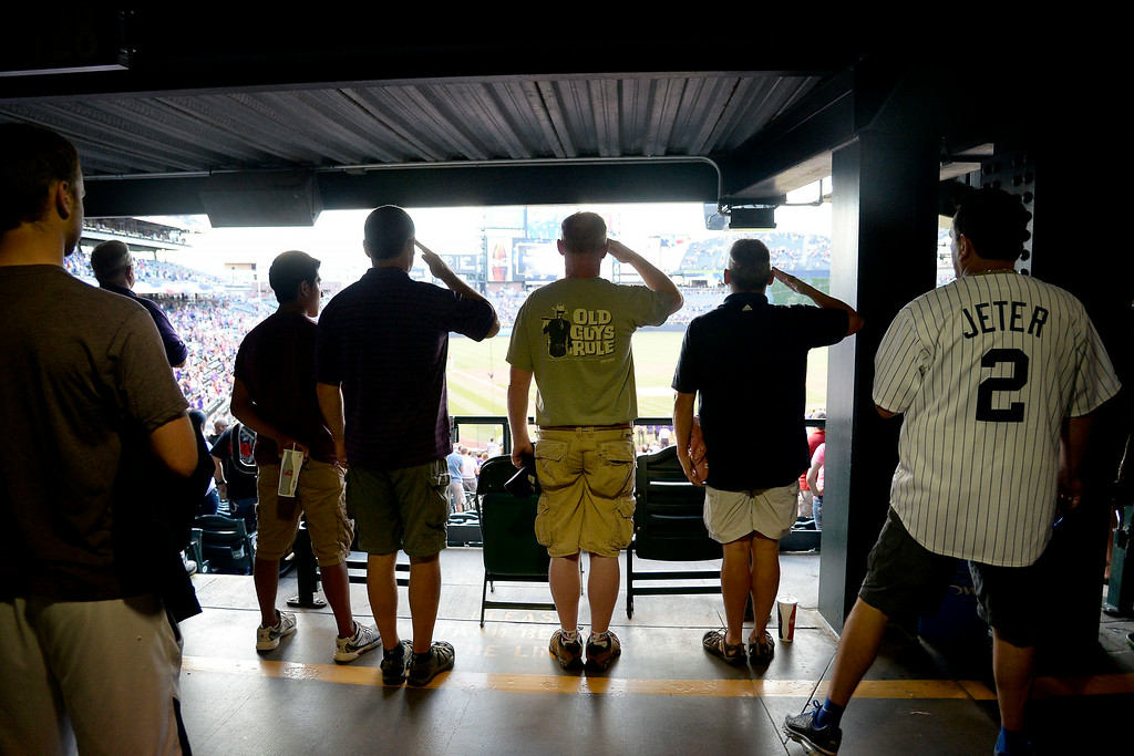 . Fans salute the flag during the playing of the national anthem before the action started at Coors Field. Major League Baseball action between the Colorado Rockies and the Washington Nationals on Monday, July 21, 2014. (Photo by AAron Ontiveroz/The Denver Post)