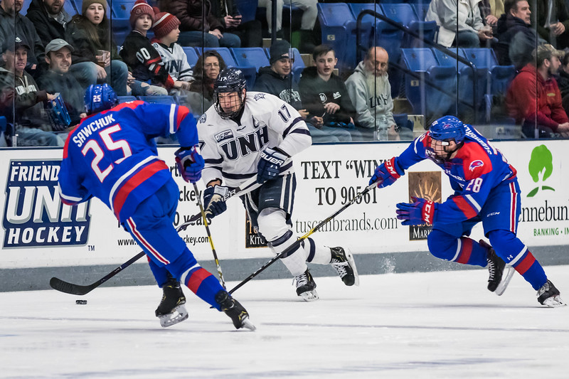 New Hampshire's Marcus Vela (17) moves the puck while being defended by Lowell's Nolan Sawchuk and Connor Sodergren during Hockey East action in Durham Friday. [Scott Patterson/Fosters.com]