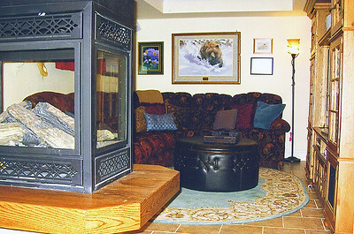 The cozy basement sports a tile floor and a peninsula fireplace that serves to help divide the space.