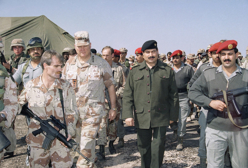 Description of . U.S. Gen. H. Norman Schwarzkopf, center, and Iraqi Lt. Gen. Sultan Hasheem Ahmad, walk under tight security towards a tent on Sunday, March 3, 1991 at a captured Iraqi air base at Safwan, Iraq for a meeting to set the terms for a permanent cease-fire. Second from left is Saudi Gen. Khalid Bin Sultan, commander of the Arab forces. (AP Photo/Pool)