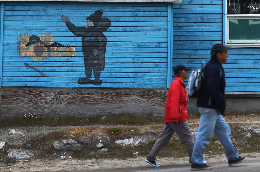 . People walk past a painting on the wall of a building  on July 18, 2013 in Ilulissat, Greenland.  (Photo by Joe Raedle/Getty Images)