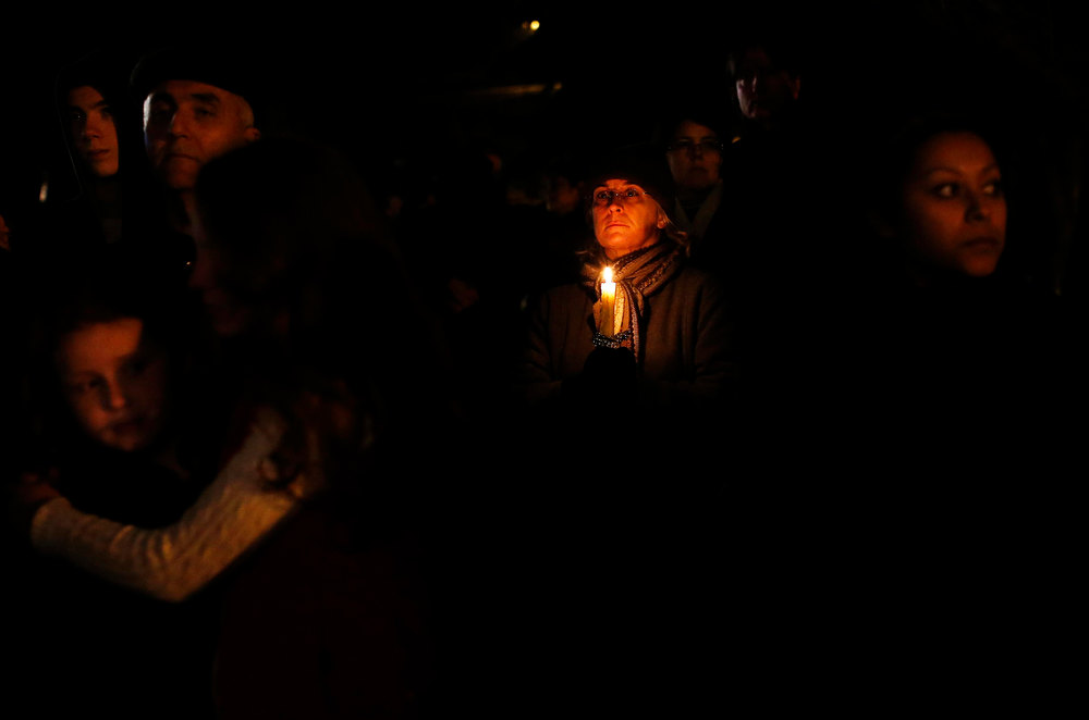 . People grieve outside the overflow area of a vigil at the Saint Rose of Lima church in Newtown, Connecticut December 14, 2012. The peace and security of the suburban Connecticut community of Newtown lay shattered on Friday after a gunman attacked a primary school in one of the worst mass shootings in U.S. history. Tearful parents and children gathered around Sandy Hook Elementary School by midday on Friday, surrounded by police vehicles, as young and old alike struggled to make sense of a shooting rampage that killed at least 28 people, including 20 children.  REUTERS/Shannon Stapleton