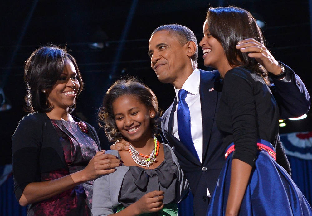 . US President Barack Obama accompanied by (from L-R ) First Lady Michelle and daughters Sasha and Malia appears on stage on election night November 6, 2012 in Chicago, Illinois. President Barack Obama swept to re-election Tuesday, forging history again by transcending a slow economic recovery and the high unemployment which haunted his first term to beat Republican Mitt Romney. AFP PHOTO/Jewel SAMAD/AFP/Getty Images