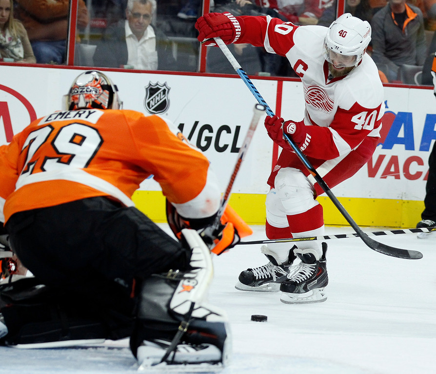. Philadelphia Flyers\' Ray Emery (29), left, defends the goal as Detroit Red Wings\' Henrik Zetterberg (40) tries to get a shot off in the third period of an NHL hockey game Saturday, Oct. 25, 2014, in Philadelphia. The Flyers won 4-2. (AP Photo/Tom Mihalek)