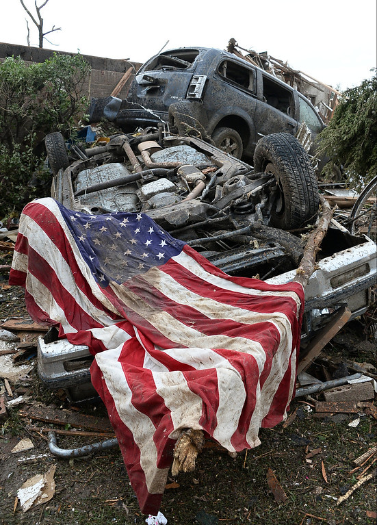 . An American flag lays on a destroyed car. 
