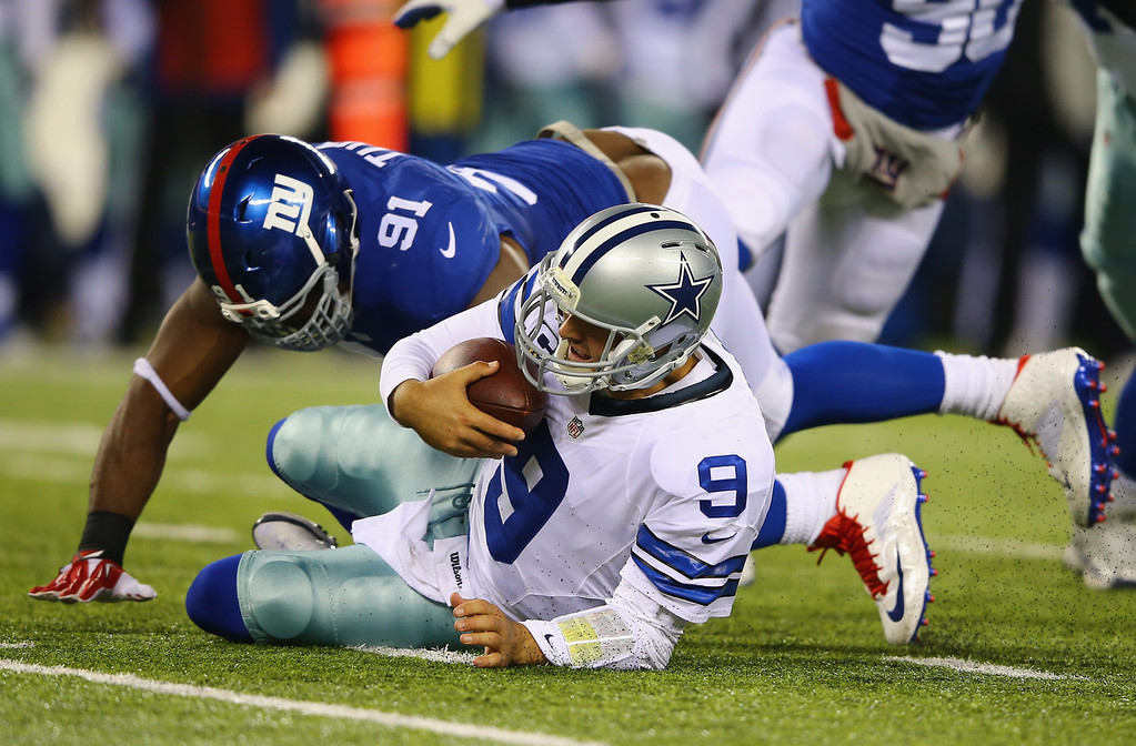 . Tony Romo #9 of the Dallas Cowboys is sacked by  Justin Tuck #91 of the New York Giants during their game at MetLife Stadium on November 24, 2013 in East Rutherford, New Jersey.  (Photo by Al Bello/Getty Images)