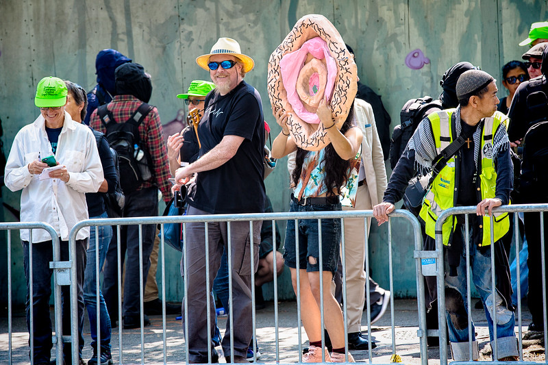 A young woman holds a blow-up vagina with an opening in the center to yell through to the far-right members across the street.