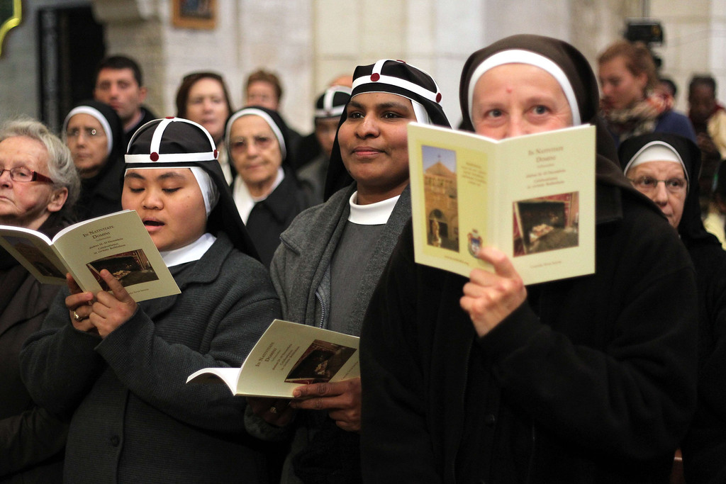 """. Nuns follow the service led by the Latin Patriarch of Jerusalem Fuad Twal (unseen), the head of the Roman Catholic Church in the Holy Land, at the Church of the Nativity as Christians gather for Christmas celebrations in the West Bank city of Bethlehem, on December 24, 2013. Thousands of Palestinians and tourists flocked into the West Bank city of Bethlehem to mark Christmas in the \""""little town\"""" where many believe Jesus Christ was born.  HAZEM BADER/AFP/Getty Images"""