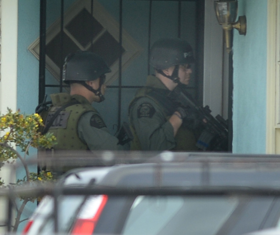 . El Monte SWAT Team members enter the home on the 11400-block of Elmcrest Street in El Monte finding the suspect dead after a standoff on Friday March 7, 2014. The suspect shot his neighbor over a dispute Friday morning. (Photo by Keith Durflinger/San Gabriel Valley Tribune)