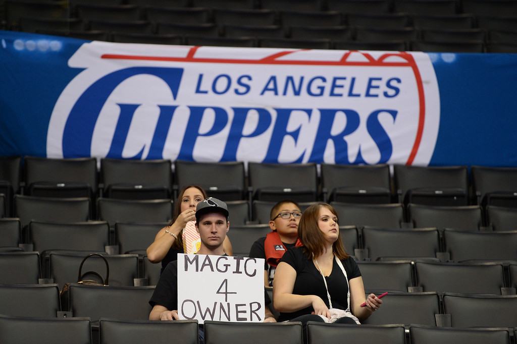 """. Fans holds a sign reading \""""Magic 4 Owner\"""" before the start of the NBA playoff game between the Los Angeles Clippers and the Golden State Warriors, April 29, 2014 at Staples Center in Los Angeles, California.  The NBA banned Clippers owner Donald Sterling from professional basketball for life over racist comments that the league\'s commissioner dubbed \""""deeply offensive and harmful.\""""   Fans and observers are speculating as to whether retired NBA superstar Magic Johnson would become new owner of the Clippers.               (ROBYN BECK/AFP/Getty Images)"""