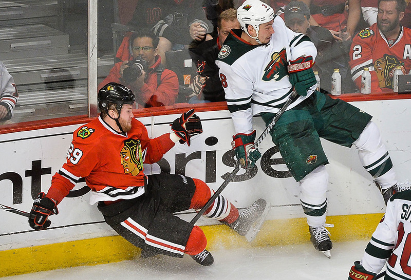 . Minnesota Wild center Cody McCormick and Chicago Blackhawks left wing Bryan Bickell slam into the wall during the third period. (Pioneer Press: Ben Garvin)