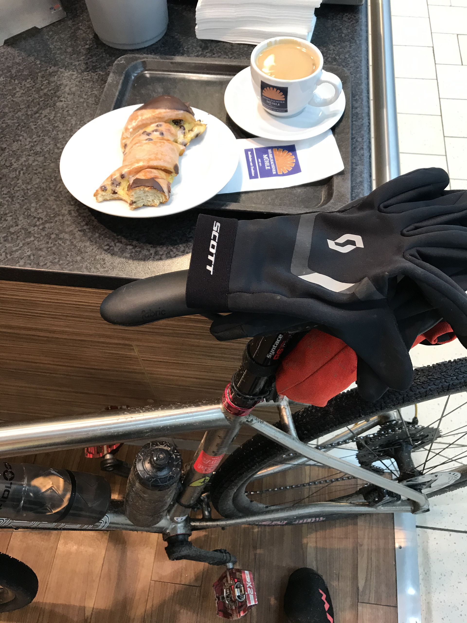 shot of a gravel bike leaning against a counter with a pastry and coffe on the counter