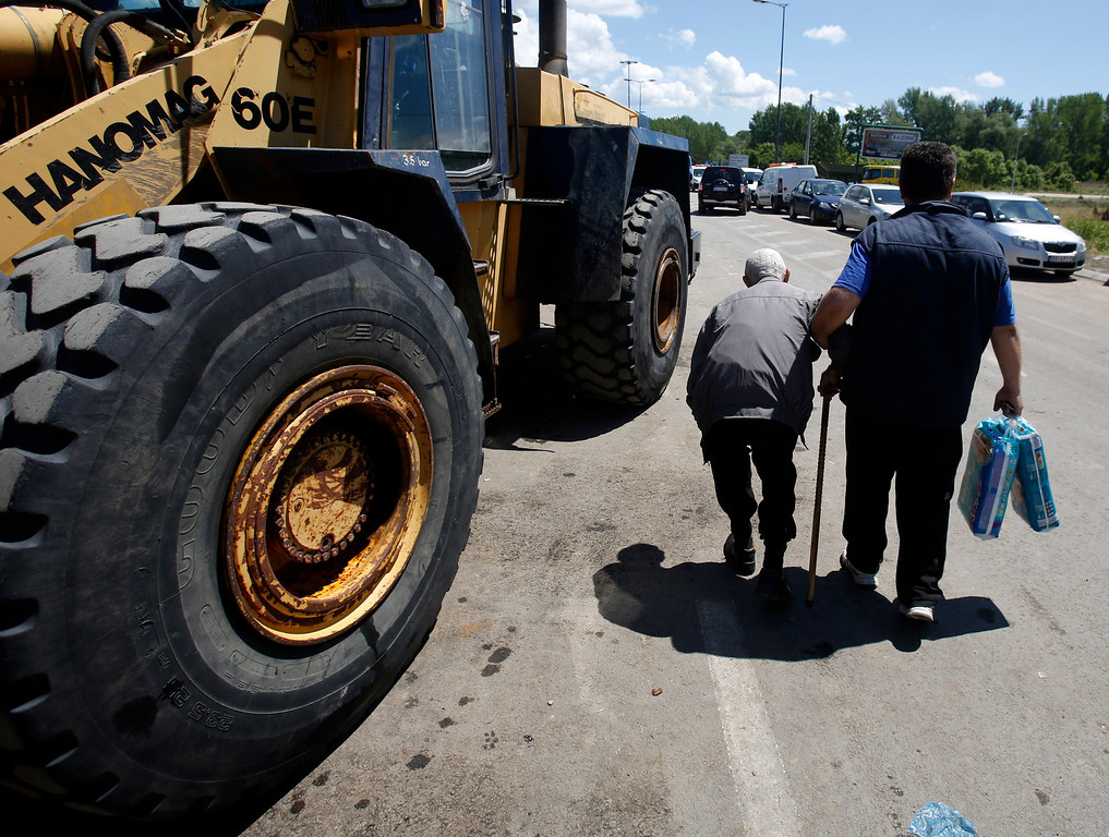 . A man helps to elderly man in Obrenovac, some 30 kilometers (18 miles) southwest of Belgrade, Serbia, Monday, May 19, 2014. Belgrade braced for a river surge Monday that threatened to inundate Serbia\'s main power plant and cause major power cuts in the crisis-stricken country as the Balkans struggle with the consequences of the worst flooding in southeastern Europe in more than a century. (AP Photo/Darko Vojinovic)