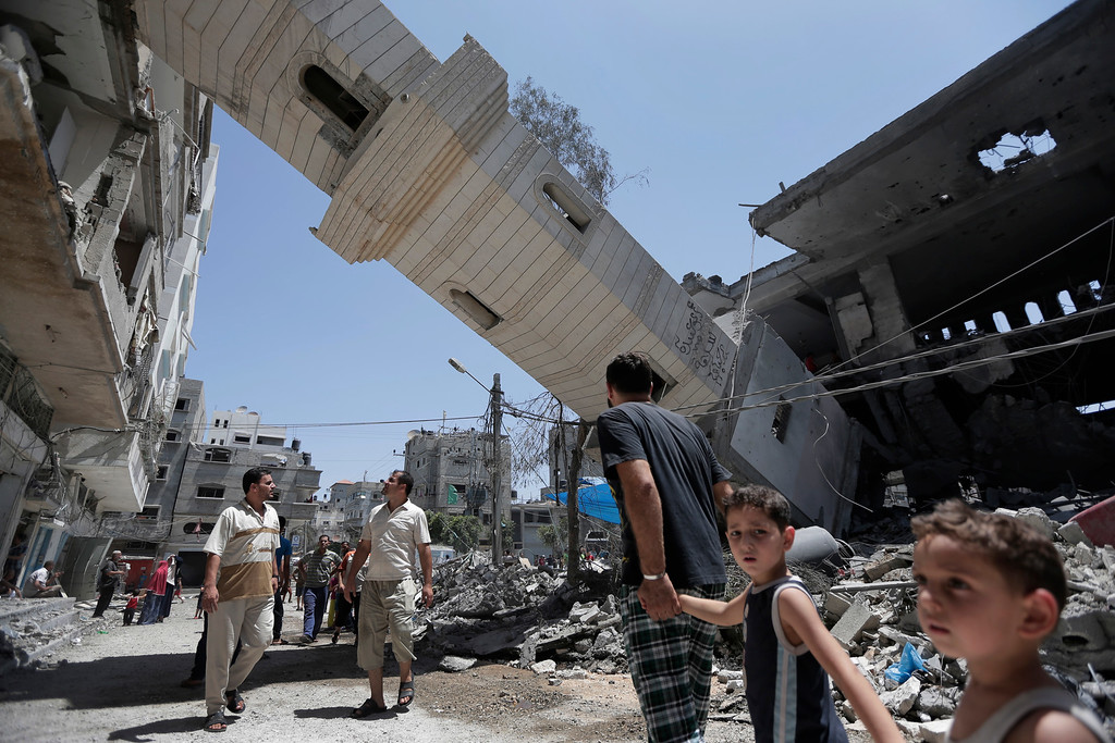 . Palestinians inspect damage to adjacent houses from a fallen minaret of the Al-Sousi mosque that was destroyed in an Israel strike, at the Shati refugee camp, in the northern Gaza Strip, Wednesday, July 30, 2014.  Israeli aircraft struck dozens of Gaza sites on Wednesday, including five mosques it said were being used by militants, while several other areas came under tank fire. (AP Photo/Lefteris Pitarakis)