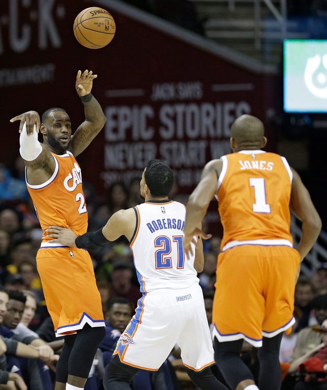 . Cleveland Cavaliers\' LeBron James (23) passes over Oklahoma City Thunder\' Andre Roberson (21) to James Jones (1) in the second half of an NBA basketball game, Sunday, Jan. 29, 2017, in Cleveland. (AP Photo/Tony Dejak)