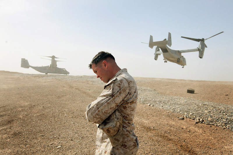 . Maj. Matt O\'Donnell of Glenelg, MD shields himself from rotor wash as Ospreys carrying the delegation of U.S. Secretary of Defense Leon Panetta leaves on March 14, 2012 at Forward Operating Base Shukvani, Afghanistan. Panetta is also scheduled to meet with President Karzai during his two-day visit to Afghanistan. The trip comes as the Taliban has vowed revenge following this past weekend\'s killing spree by a U.S. soldier who is accused of killing 16 civilians in Afghanistan. Most of those killed were children and women.  (Photo by Scott Olson/Getty Images)