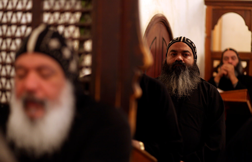 Description of . Clergymen pray during an early morning mass at the historic al-Muharraq Monastery, a centuries-old site some 180 miles (300 kilometers) south of Cairo in the province of Assiut, Egypt, Tuesday, Feb. 5, 2013. Egypt\'s Coptic Christian pope sharply criticized the country\'s Islamist leadership in an interview with The Associated Press on Tuesday, saying the new constitution is discriminatory and Christians should not be treated as a minority. (AP Photo/Khalil Hamra)