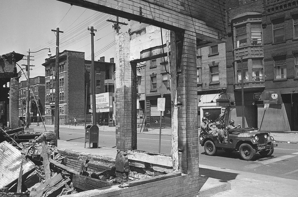 . Peaceful now, but a scene of rioting and violence three nights ago, Hough Street is traveled only by official business vehicles. A jeep-load of National Guardsmen pass a burned-out store in the riot area in Cleveland, Ohio, July 22, 1966 as the city readies itself for a possible fourth night of trouble. (AP Photo)