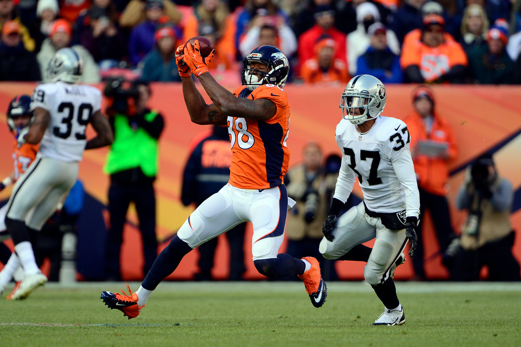 . DENVER, CO - DECEMBER 28: Demaryius Thomas (88) of the Denver Broncos makes a catch with Chance Casey (37) of the Oakland Raiders chasing him down in the second quarter.  The Denver Broncos played the Oakland Raiders at Sports Authority Field at Mile High in Denver on December, 28 2014. (Photo by Joe Amon/The Denver Post)