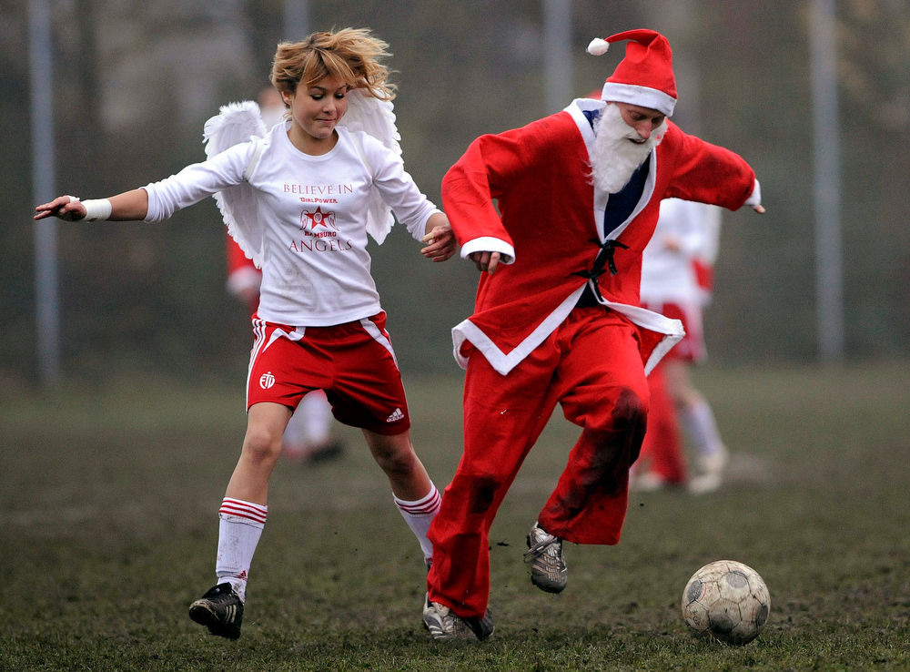 . Members of the soccer teams of Angles and Santa Claus challenge for the ball during their charity Christmas soccer match in Hamburg, Germany, on Saturday, Dec. 6, 2008.  The charity match between a youth girls team and a 5th division Hamburg men\'s team is played as a fundraising match for the Uwe Seeler Foundation, and ended in a 10-10 draw. (AP Photo/Fabian Bimmer)