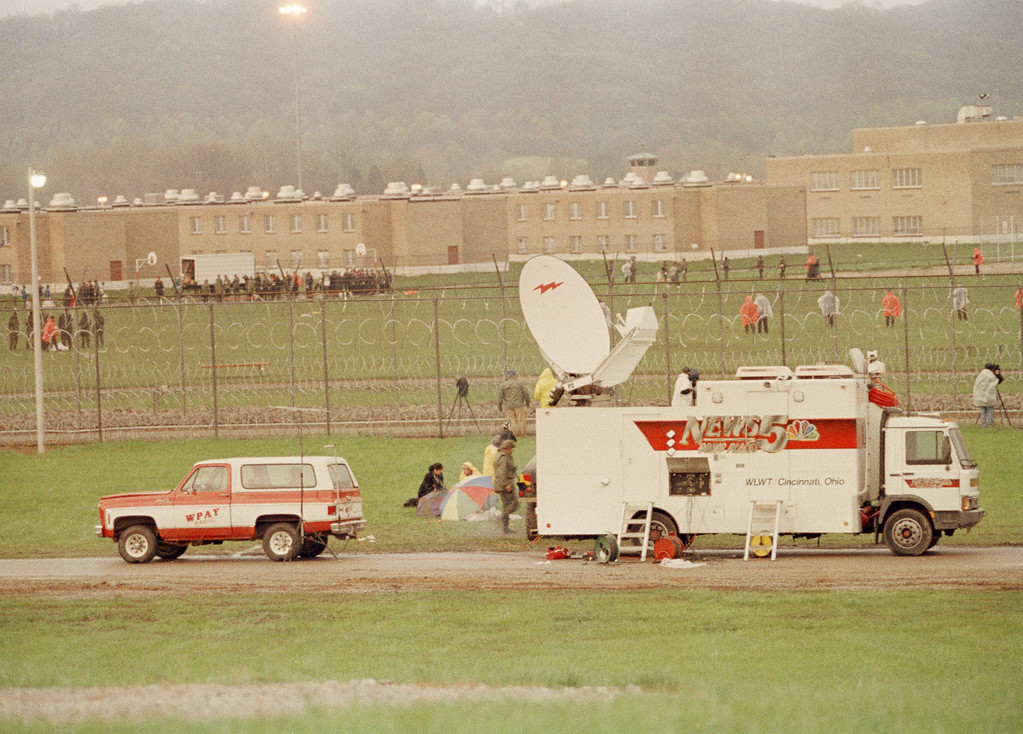 . A television satellite truck and a radio station broadcast truck sit outside the Southern Ohio Correction Facility in Lucasville, Ohio, April 21, 1993, for a live broadcast of the surrender of 450 inmates who had barricaded themselves in a cell block following an Easter Sunday riot. The cell block and surrender are shown in background. One guard and seven inmates died in the siege. (AP Photo/Lennox McLendon)